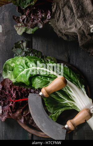 Variety of fresh chard mangold salad leaves on woode chopping board with vintage knife and sackcloth rag over old - Stock Photo