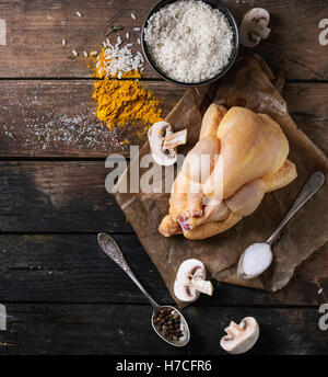 Whole raw mini chicken on baking paper with seasoning in vintage spoons, sliced mushrooms and bowl of uncooked white - Stock Photo
