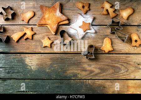 Homemade Christmas shortbread star shape sugar cookies different size with sugar powder and cookie cutters on old - Stock Photo