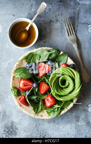Mixed salad with spinach,berries and avocado rose with honey mustard dressing.Top view - Stock Photo