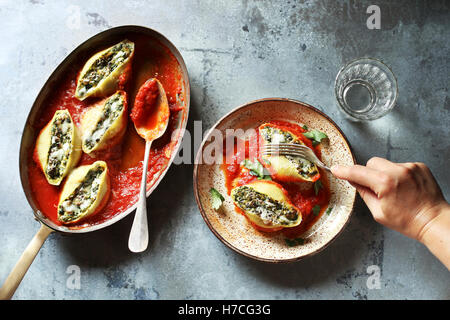Female eating stuffed pasta shells with ricotta cheese and spinach - Stock Photo