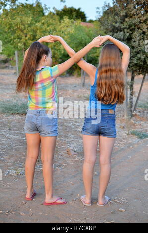 Best Friends Forever - two 12 year old teenage girls  holding hands in an infinity forever sign to signify BFF - Stock Photo