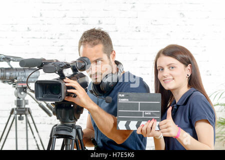 a cameraman and a young woman with a movie camera and clapper - Stock Photo