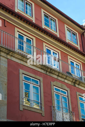 Blue sky reflected in windows of a red building in Braga, Portugal - Stock Photo