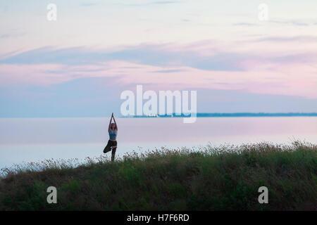 Beautiful athletic girl doing yoga against the sea. - Stock Photo