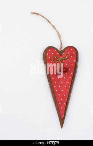 A red decorative wooden heart on the snow. - Stock Photo