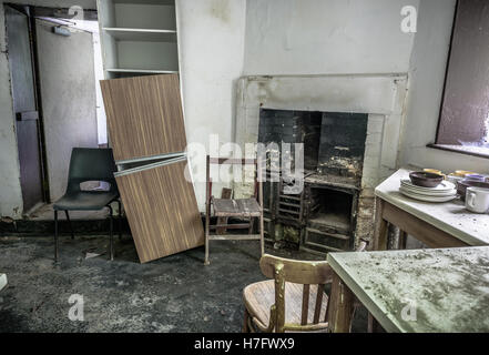 An old, abandoned kitchen with old cast iron fireplace. - Stock Photo