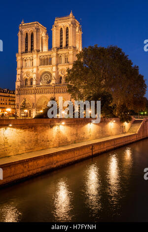 Notre Dame de Paris cathedral illuminated at twilight with the Seine River on Ile de La Cite. Paris, France - Stock Photo
