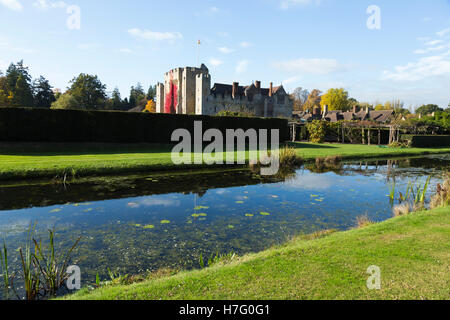 Hever Castle & moat, former home of Anne Boleyn, clad with red autumnal virginia creeper & blue sky / sunny skies - Stock Photo