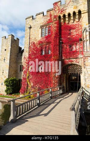 Hever Castle clad with red autumnal virginia creeper: Blue sky / sunny skies / sun & drawbridge / draw bridge over - Stock Photo