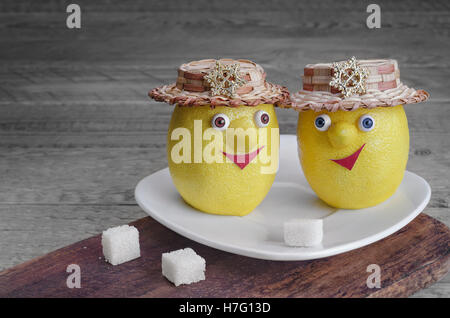 Lemons with sugar on a white plate and grey wooden background - Stock Photo