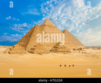 All Egyptian Pyramids from distance with row of camels walking in foreground in Giza, Cairo, Egypt.  Wide telephoto - Stock Photo