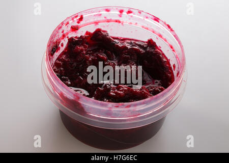 Black currant jam in the round plastic container on white background - Stock Photo