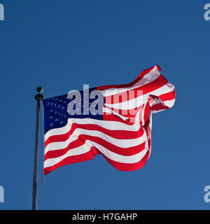 American flag on flagpole blowing in wind - Stock Photo