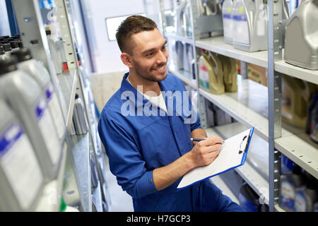 smiling auto mechanic with clipboard at car shop - Stock Photo