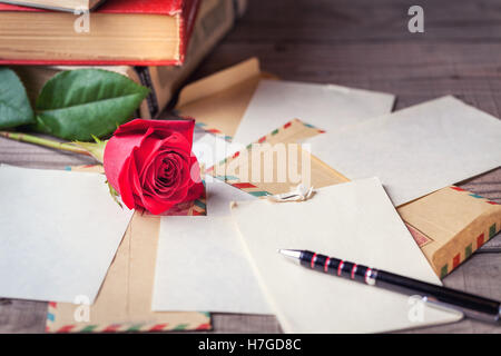Vintage envelopes, red rose and sheets of paper scattered on the wooden table for writing romantic letters. - Stock Photo
