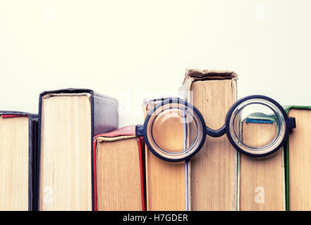 Black round glasses lay on top of a pile of battered old books. Copy space - Stock Photo