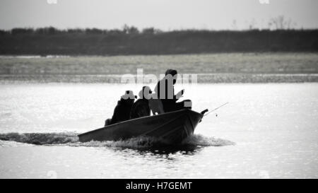 Black and white rendering of the silhouette of three unrecognizable fishermen in Moss Landing, CA, USA - Stock Photo