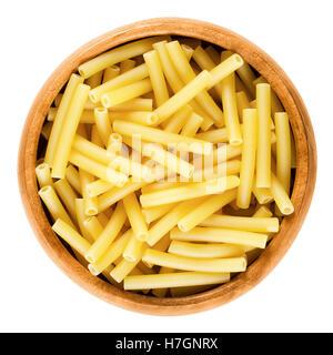 Macaroni pasta in wooden bowl, Italian maccheroni, short-cut noodles in the shape of narrow tubes. - Stock Photo