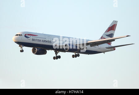 A British Airways airplane takes off from Heathrow airport as the sun sets. - Stock Photo