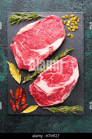 Two pieces of raw meat beef on a slate plate with rosemary - Stock Photo