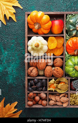 Set of autumn vegetables, fruits, nuts and seeds in a wooden box with cells top view with copy space - Stock Photo