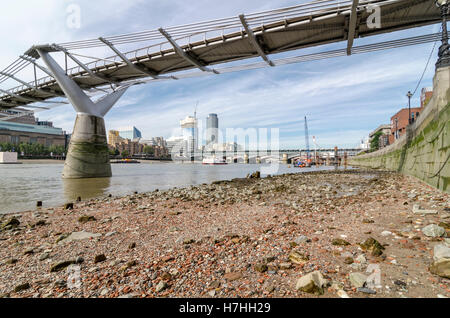 North bank of the River Thames at low tide under Millennium Bridge - Stock Photo