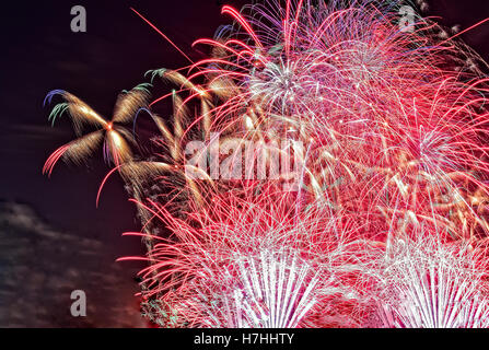 Close view of colorful bouquets of fireworks in the night sky on the night of 31 December to 1 January. close, horizontal - Stock Photo