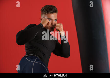 Photo of boxer fulfills blows, on red background - Stock Photo