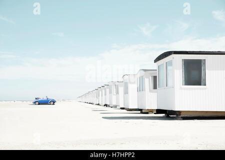 Blue VW Beetle cabriolet faces white beach huts, beach of Loekken, Løkken, Denmark - Stock Photo