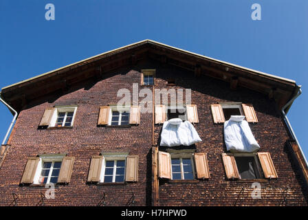 Bedlinen hanging out of the windows in a wooden house in Glas, canton of Grisons, Switzerland, Europe - Stock Photo