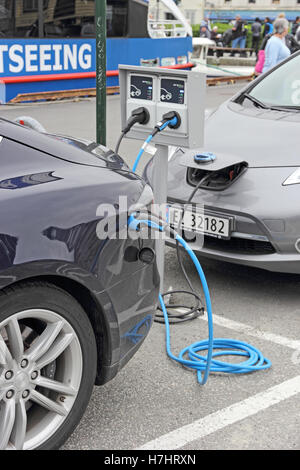 Tesla and Nissan Leif electric cars at recharging point in car park, Stavanger, Norway - Stock Photo