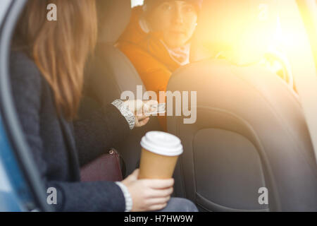 Brunette sitting in taxi sends cash for passage driver - Stock Photo