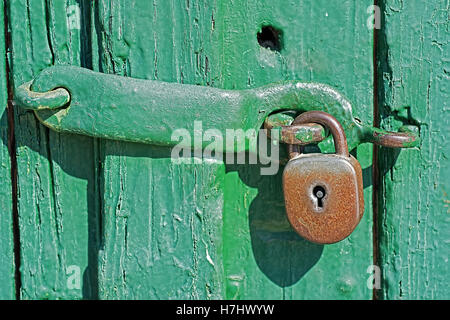 Old Rusty Padlock on Green Wooden Door - Stock Photo