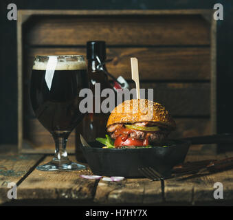 Beef burger with crispy bacon, vegetables and beer - Stock Photo