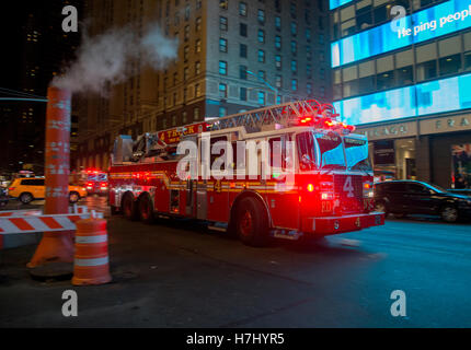 New York fire truck rushes past a steam vent on 7th Avenue - Stock Photo