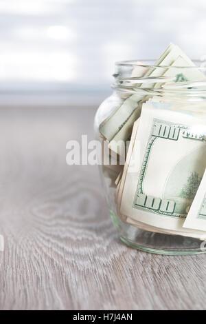 Money. Dollars in open jar on grey wooden background