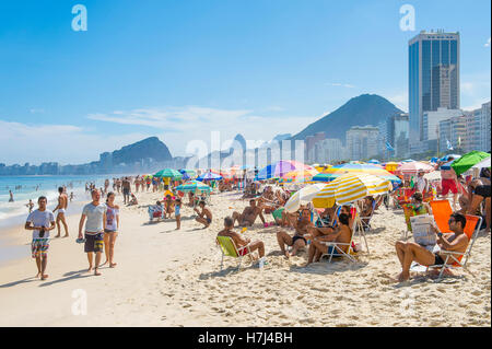 RIO DE JANEIRO - FEBRUARY 27, 2016: Crowds of beachgoers fill Copacabana Beach with colorful umbrellas on a bright - Stock Photo