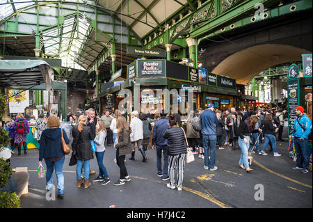 LONDON - OCTOBER 31, 2016: Visitors browse the specialty food stalls at Borough Market, one of the city's largest - Stock Photo