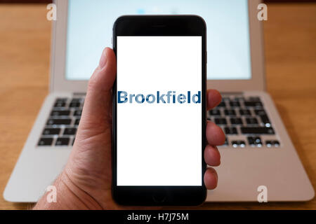 Using iPhone smartphone to display logo of Brookfield the global alternative asset manager - Stock Photo