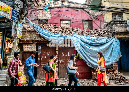 People walk through an alley where houses damaged by 2015 earthquakes still stand in Thamel area, Kathmandu. © Reynold - Stock Photo