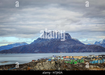 Colorful living blocks of Nuuk city at the fjord, Sermitsiaq mountain in the background, Greenland - Stock Photo