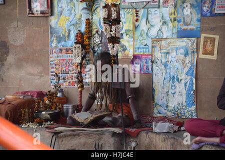 Indian sadhu sitting and reading with images of indian gods in Varanasi, Uttar Pradesh, India - Stock Photo