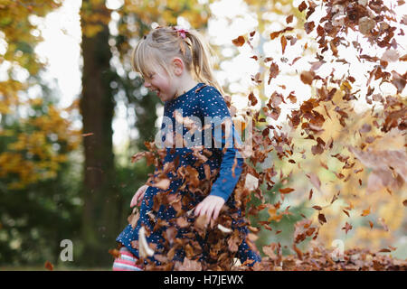 Happy autumn. Little girl playing in dry leaves pile in autumn park.