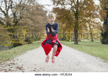Happy autumn. Little girl in red coat jumping in autumn park. - Stock Photo