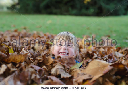 Happy autumn. Little girl looking out of dry leaves pile in autumn park. - Stock Photo