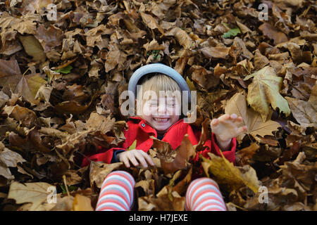 Happy autumn. Little girl in red coat playing with  pile of dry leaves in autumn park. - Stock Photo