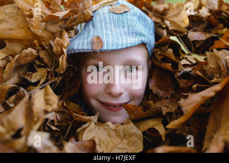 Happy autumn. Boy in retro flat cap looking out of dry leaves pile in autumn park. - Stock Photo