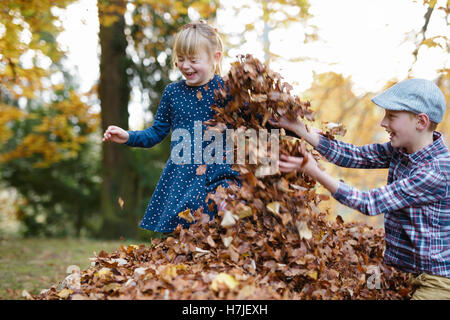 Happy autumn. Two kids playing in dry leaves pile in autumn park. - Stock Photo