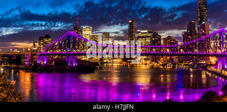 Vibrant night time panorama of Brisbane city with Story Bridge - Stock Photo